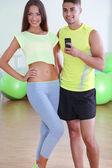Garoto e garota fotografando no espelho no telefone na sala de fitness — Fotografia Stock