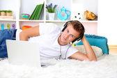 Genç adam laptop ile halı üzerinde rahatlatıcı — Stok fotoğraf