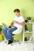 Young man relaxing with laptop in armchair, on home interior background — Stock Photo