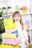 Little girl with presents near Christmas tree in room — Stock Photo