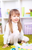 Little girl with presents in room — Stock Photo