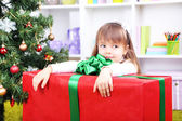 Little girl with big present box near Christmas tree in room — Stock Photo