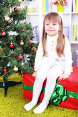 Little girl setting on big present box near Christmas tree in room — Stock Photo
