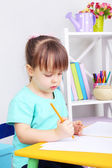 Little girl draws sitting at table in room — Stock Photo