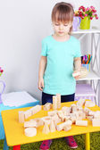 Little girl plays with construction blocks on table in room — Stock Photo