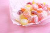 Sweet multicolor candies on paper, on color background — Foto de Stock