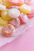 Sweet multicolor candies on paper, on color background — Stock Photo