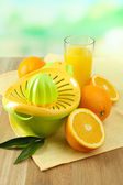 Citrus press and oranges on table on blue background — Stock Photo