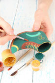 Hands paints on and made ceramic saint patricks day boot and art materials — Stock Photo