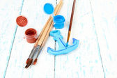 Hand made ceramic anchor and color paints on wooden table — Foto Stock