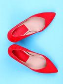 Bonitos sapatos femininos vermelhos, sobre fundo azul — Foto Stock