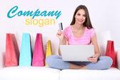 Bela jovem segurando laptop com sacos de compras no sofá no fundo branco — Fotografia Stock