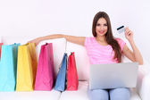 Beautiful young woman holding laptop with shopping bags on sofa on white background — Stock Photo
