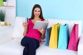 Tableta de celebración hermosa joven con bolsas de compras en sofá sobre fondo azul — Foto de Stock