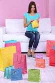 Beautiful young woman sitting on sofa with shopping bags on pink background — Stock Photo