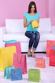 Bela jovem sentada no sofá com sacos de compras em fundo rosa — Fotografia Stock