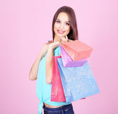 Beautiful young woman holding shopping bags on pink background — Fotografia Stock