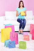 Beautiful young woman sitting on sofa with shopping bags on pink background — Foto de Stock