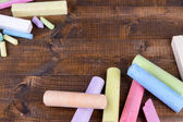 Chalks in variety of colors, on wooden background — Stockfoto
