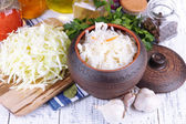 Composition with fresh and marinated cabbage (sauerkraut), spices, on wooden table background — Stock Photo