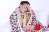 Guy wrapped in plaid lies on sofa on white background — Stock Photo