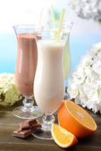 Milk shakes with fruits on table on light blue background — ストック写真