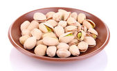 Pistachio nuts on plate isolated on white — Stock Photo