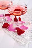 Komposition mit pink sparkle wein in gläsern und rosenblüten, isoliert auf weiss — Stockfoto