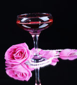 Composition with pink sparkle wine in glass and rose isolated on black — Стоковое фото