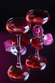 Composition with pink wine in glasses and rose petals on dark color background — Stock Photo