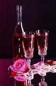 Komposition mit rosé im glas, flasche und rosen auf dunkle farbe hintergrund — Stockfoto
