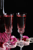 Composition with pink wine in glasses, bottle and roses isolated on black background — Stockfoto