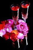 Komposition mit rosé im glas, flasche und rosen auf schwarzem hintergrund isoliert — Stockfoto
