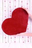 Hands holding big red heart on wooden background — Stockfoto