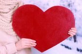 Female holding big red heart on bright background — Stock Photo
