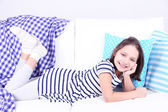 Beautiful little girl lying on sofa, on home interior background — Stock Photo