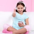 Beautiful little girl sitting on sofa and listening to music, on home interior background — Stock Photo #40820115