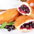 Fresh baked pasties with currant on plate on table close-up — Stock Photo #40823507