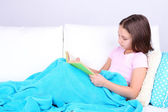 Beautiful little girl sitting on sofa with book, on home interior background — Stock Photo