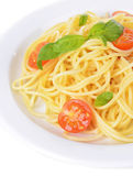 Delicious spaghetti with tomatoes on plate close-up — Stock Photo