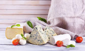 Different tasty cheese, on wooden table — Foto Stock