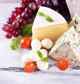 Different tasty cheese, on wooden table — Stockfoto