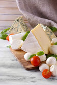 Different tasty cheese, on wooden table — Stock fotografie