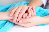 Medical doctor holding hand of patient, on light background — Stock Photo