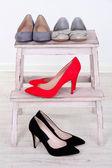 Beautiful female shoes on wooden shelf — Stock Photo