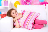 Pretty little girl slipping on sofa on celebratory background — Stock Photo