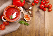 Tasty tomato soup and vegetables on wooden table — Stock Photo