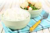 Cooked rice with vegetables on wooden table close up — Stock Photo