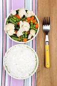 Cooked rice with vegetables on wooden table — Stock Photo