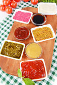 Various sauces on chopping board on table close-up — Stock Photo